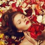 Stående av den trendiga rödhåriga modellen (för ingefäran) i rosa kronblad Royaltyfri Fotografi