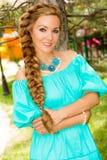 Stående av den unga härliga le kvinnan med långt hår och utomhus- Royaltyfri Fotografi