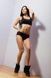 Stående av den unga kvinnan för härlig brunett med det perfekta diagramet som ler att stå i svart sportwear och fnissanden på den Arkivbilder