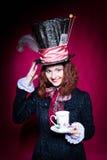 Stående av den unga kvinnan för smilimg i similituden av hattmakaren Arkivbild