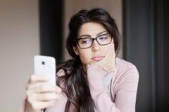 Stående av den unga ledsna kvinnan som inomhus mottar dåliga sms Fotografering för Bildbyråer