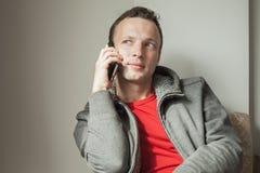 Stående av den unga vuxna Caucasian mannen som talar på mobiltelefonen Arkivfoton