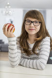 Stående av det hållande äpplet för tonårs- flicka, medan sitta på tabellen i hus Royaltyfri Fotografi