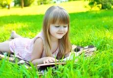 Stående av det lilla le flickabarnet som läser en bok Arkivbilder