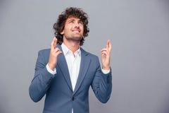 Stående av en affärsman som ber med korsade fingrar Arkivfoto
