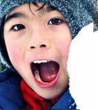 Stående av en asiatisk pojke som skriker ha gyckel i snön Arkivfoton