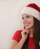 Stående av en attraktiv kvinna i jultomtenhatt som drömmer om Chri Royaltyfri Fotografi