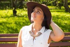Stående av en attraktiv smilling kvinna med hatten i parkera på en solig dag Arkivfoto