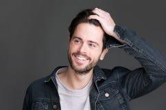 Stående av en attraktiv ung man som ler med handen i hår Arkivfoto