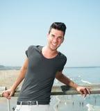 Stående av en attraktiv ung man som ler på sjösidan Arkivbild