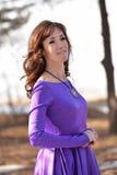 Stående av en brunett i en violett klänning Royaltyfri Bild
