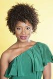 Stående av en elegant afrikansk amerikan i av en skuldraklänning som ler över kulör bakgrund Royaltyfri Foto