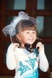 Stående av en flicka i en hatt med en skyla och en gammal retro telefon i hand Royaltyfri Bild