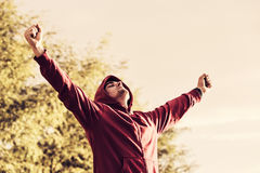 Stående av en gladlynt ung man med öppen armspridning utomhus Arkivbild