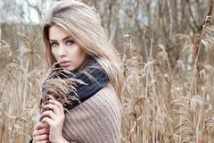 Stående av en härlig flicka med blåa ögon i ett grått omslag i fältet bland träd och högväxt torrt gräs som tonas i skuggor av gr Arkivbilder