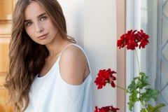 Stående av en härlig gullig flicka med blåa ögon och mörkt lockigt hår i borggården nära väggen med fönstret och blommorna Royaltyfri Foto