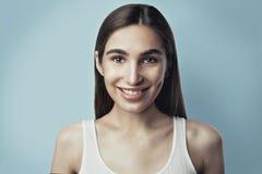 Stående av en härlig kvinna som ler, skönhetfrikändhud, blå bakgrund Arkivbild
