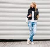 Stående av en härlig ung blond flicka med långt hår som poserar på en gata med kaffe och en ryggsäck Utomhus- varm färg Royaltyfri Bild