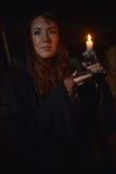 Stående av en kvinna i mörkret med en stearinljus Royaltyfri Bild