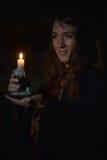 Stående av en kvinna i mörkret med en stearinljus Royaltyfria Bilder
