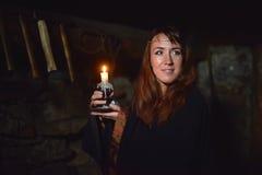 Stående av en kvinna i mörkret med en stearinljus Royaltyfri Foto