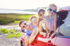 Stående av en le familj med två barn på stranden i cet Royaltyfria Foton