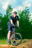 Stående av en manidrottsman nen på en cykel Royaltyfria Bilder