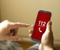 Stående av en mogen man som kallar nödlägenummer i en mobil Royaltyfri Foto