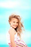 Stående av en nätt liten flicka med att vinka i de långa mumlen för vind Fotografering för Bildbyråer