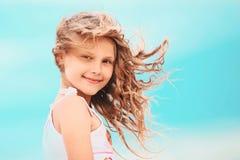 Stående av en nätt liten flicka med att vinka i de långa mumlen för vind Arkivfoto