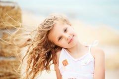 Stående av en nätt liten flicka med att vinka i de långa mumlen för vind Royaltyfri Bild
