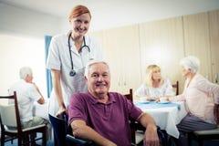 Stående av en sjuksköterska med den höga mannen i rullstol Royaltyfri Bild