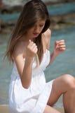 Stående av en tonårig flicka med den vita klänningen på stranden Arkivbilder