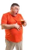Stående av en törstig fet man som stirrar på ett exponeringsglas av öl Royaltyfri Foto
