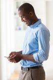 Stående av en ung afrikansk amerikanaffärsman som använder en mobil Arkivbild