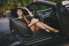 Stående av en ung dam i bilen i en stor svart hatt Fotografering för Bildbyråer