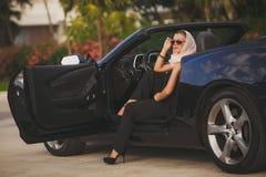 Stående av en ung dam i en svartcabriolet Royaltyfri Foto
