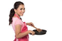 Stående av en ung hemmafru som är klar att laga mat Arkivbild