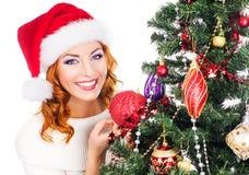 Stående av en ung kvinna som poserar nära julgranen Fotografering för Bildbyråer