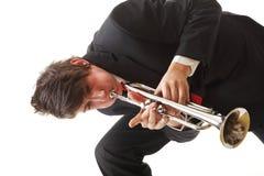 Stående av en ung man som spelar hans trumpet Arkivbild