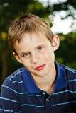 Stående av en ung pojke som sitter i trädgården Fotografering för Bildbyråer