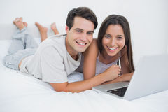 Stående av ett par genom att använda en bärbar dator som ligger i säng Royaltyfri Fotografi