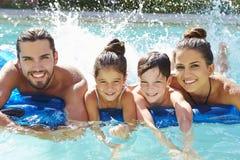 Stående av familjen på luftmadrass i simbassäng Arkivbild