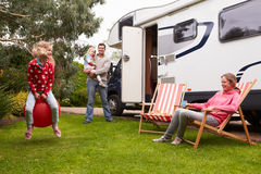 Stående av familjen som tycker om campa ferie i campareskåpbil Fotografering för Bildbyråer