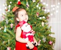 Stående av fazakh, asiatisk barnflicka runt om en dekorerad julgran Unge på nytt år för ferie Royaltyfri Foto