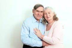 Stående av franka höga par som tycker om deras avgång Den tillgivna åldringen kopplar ihop med härligt stråla vänligt leendepos. Arkivfoto