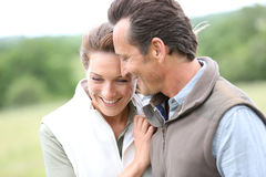Stående av glade medelåldersa par som går i natur Royaltyfria Bilder