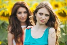 Stående av härliga två lyckliga unga kvinnor med långt hår in Arkivfoton
