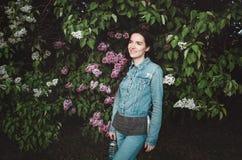 Stående av härligt le, ung kvinna som är utomhus- med purpurfärgade lila blommor för blomning i vårträdgård _ Arkivfoton