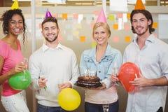 Stående av kollegor som tycker om födelsedagpartiet Fotografering för Bildbyråer